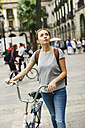 Spain, Barcelona, young woman pushing bicycle in the city - EBSF000986