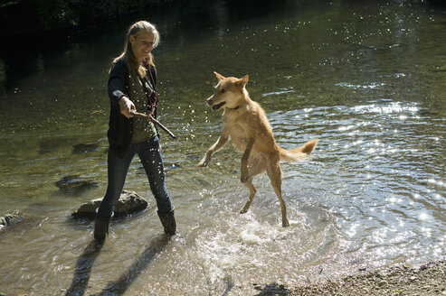 Young woman playing with her dog in nature - CRF002719