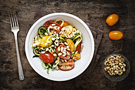 Helically coiled courgette, vegetable noodles and tomatoes in bowl - EVGF002473