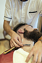 Barber shaving beard of a customer - MGOF000909