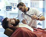 Barber cutting beard of a customer - MGOF000912