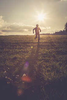 Silhouette of boy running on a meadow at backlight - SARF002233
