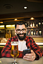 Smiling hipster sitting in a pub looking at his smartphone - JASF000232