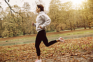 Woman jogging in park during autumn - MFF002451