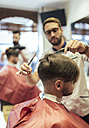 Barber cutting hair of a customer with twin brother in background - MGOF000925