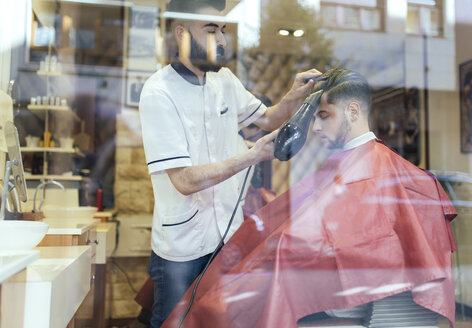 Barber blow-drying hair of a customer in a barber shop - MGOF000928