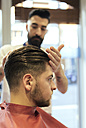 Barber cutting hair of a customer - MGOF000931