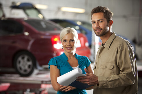 Smiling man and customer in repair garage with ckeck list - SELF000075