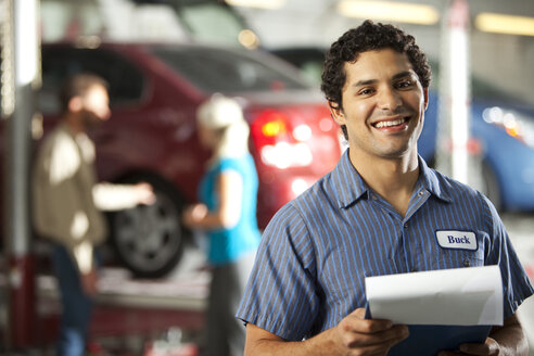 Smiling man in repair garage holding clipboard with ckeck list - SELF000078