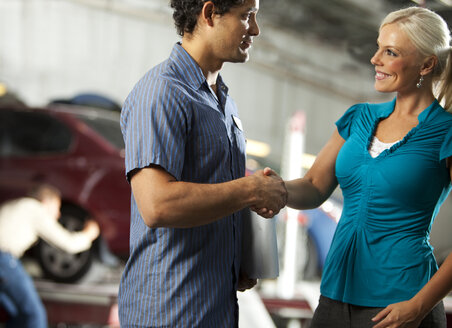 Man and customer in repair garage shaking hands - SELF000081