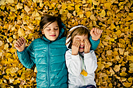 Two girls lying side by side on ground covered with autumn leaves - LVF004045