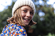 Portrait of smiling girl wearing woollen cap looking over her shoulder - MGOF000947