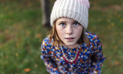 Portrait of girl wearing woollen cap looking up - MGOF000950
