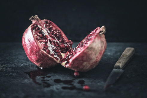 Sliced pomegranate and a kitchen knife on slate - IPF000260