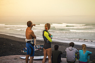 Indonesia, Bali, back view of five surfers on the beach looking to the sea at twilight - KNTF000136