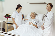 Senior woman in hospital talking to nurse and female dotor - MFF002462