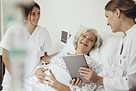 Senior woman in hospital talking to doctor and nurse - MFF002465