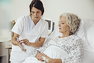 Nurse explaining senior woman in hospital digital tablet - MFF002468
