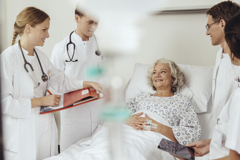 Senior woman in hospital talking to doctors during ward round - MFF002471