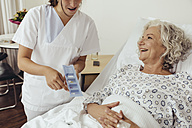 Nurse explaining medication to senior woman in hospital - MFF002474