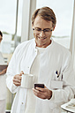 Doctor with coffee cup and smartphone - MFF002480