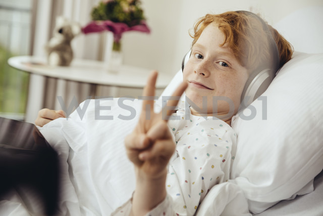 Sick boy lying in hospital making victory sign, wearing head phones - MFF002492