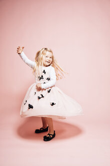 Smiling blond little girl dancing in front of pink background - IPF000262