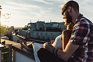 Austria, Vienna, Young couple enjoying romantic sunset on rooftop terrace - AIF000119