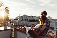 Austria, Vienna, Young couple enjoying romantic sunset on rooftop terrace - AIF000122