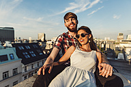 Austria, Vienna, Young couple enjoying romantic sunset on rooftop terrace - AIF000125