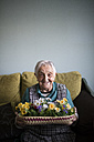 Portrait of senior woman showing a basket decorated with artificial flowers - RAEF000571