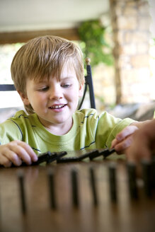Portrait of little boy playing with domino - RMAF000011
