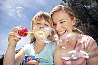 Woman and her little daughter blowing soap bubbles - RMAF000026