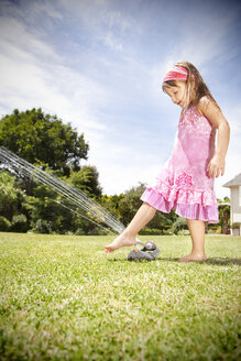 Little girl playing with lawn sprinkler in the garden - RMAF000029