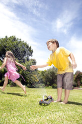 Two little children playing with lawn sprinkler in the garden - RMAF000032