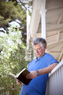 Man leaning against balustrade reading a book - RMAF000038