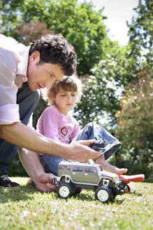 Man and his little daughter with toy car in the garden - RMAF000053
