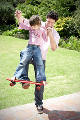 Man playing with his little daughter in the garden - RMAF000056
