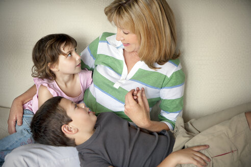 Little boy and girl with their grandmother on the couch - RMAF000062