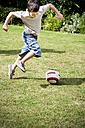 Little boy playing soccer in the garden - RMAF000071