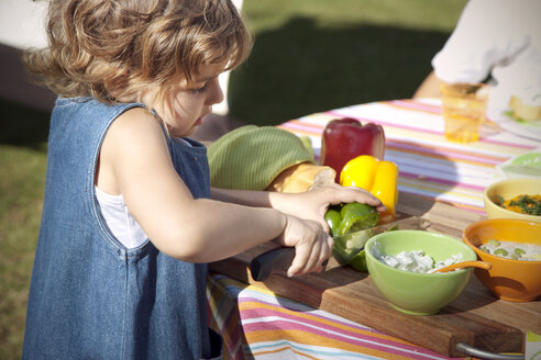 Little girl choping bell pepper on table in the garden - RMAF000077