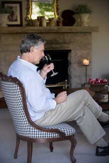 Man with glass of red wine sitting in the living room - RMAF000080
