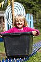 Portrait of litte blond girl sitting in a soap box - JFEF000731