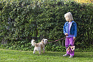 Little girl standing on a meadow with her mongrel - JFEF000734