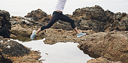 Spain, Ferrol, jogger jumping over water at the coast. - RAEF000577