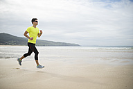Spain, Ferrol, young man jogging on the beach - RAEF000579