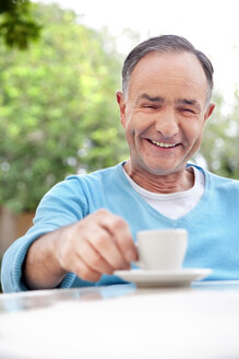 Portrait of smiling mature man sitting with cup of coffee - RMAF000088