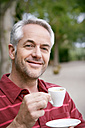 Portrait of smiling man with cup of coffee - RMAF000091