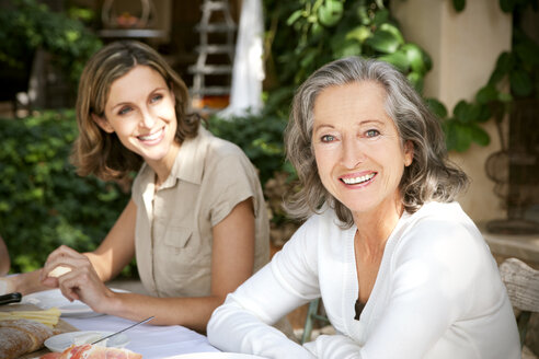 Portrait of smiling mature woman and young woman in the background - RMAF000097