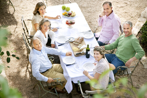Six friends sitting at laid table in the garden looking up to camera - RMAF000109